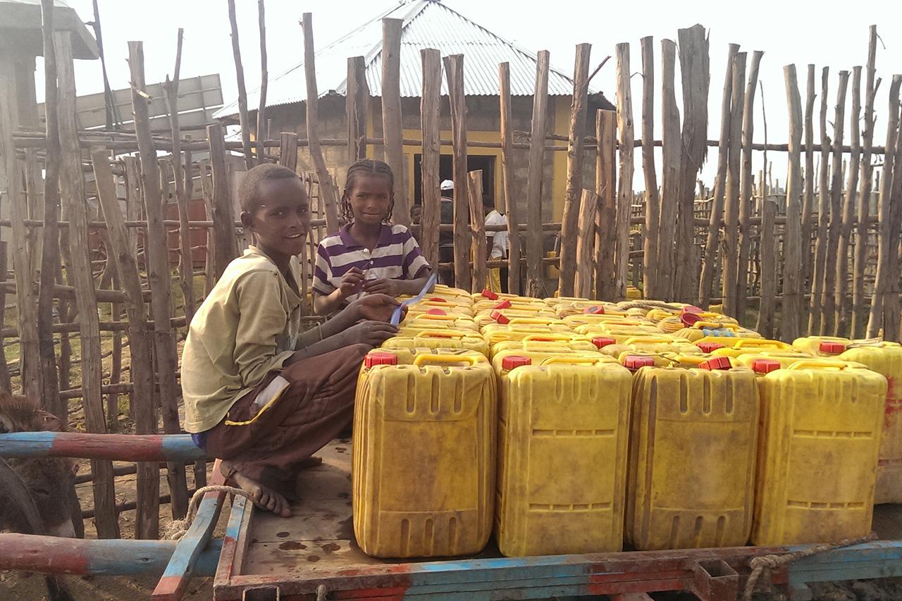 2014 Äthiopien - Kinder mit Kanistern, gefüllt mit dem Wasser des Solarbrunnens
