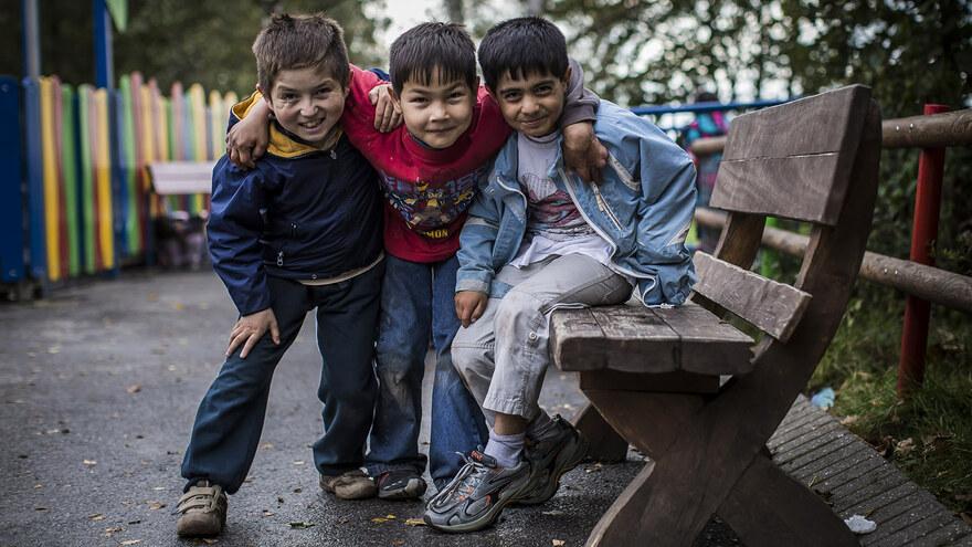 Drei glückliche Kinder aus dem Friedensdorf Oberhausen lächeln in die Kamera