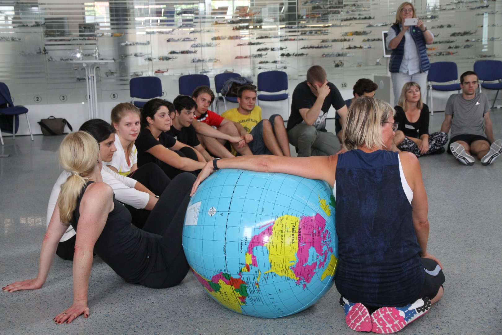 Eine Gruppe Jugendliche sitzt im Halbkreis auf dem Boden